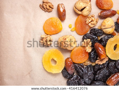 candied roasted nuts, dried fruits, dried pineapple, dried figs, walnuts, prunes, figs, dried apricots on a paper background - stock photo