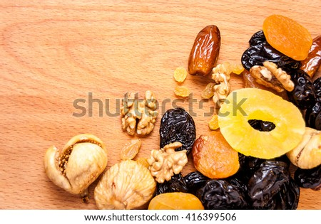 candied roasted nuts, Grilyazh and dried fruits, dried pineapple, dried figs, walnuts, prunes, figs, dried apricots, candied roasted nuts on the wooden desk  - stock photo
