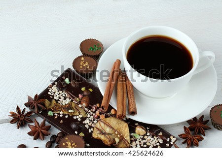 candies and chocolates with cinnamon and anise with coffee beans on white wooden background with Cup of strong coffee - stock photo