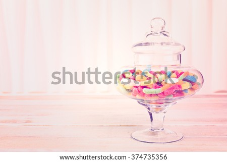 Candies in candy jar on wood table. - stock photo