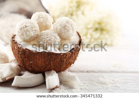 Candies in coconut flakes and fresh coconut on  light wooden background - stock photo