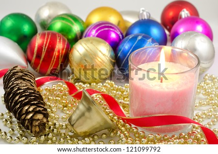 Candle and bell in front of christmas balls