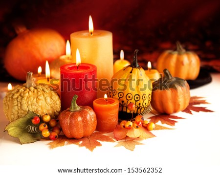 Candle and pumpkins on a autumn background - stock photo