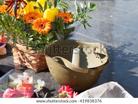 candle burning in a helmet at the monument in victory day - stock photo