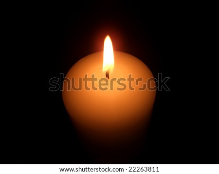 Candle burning in darkness.