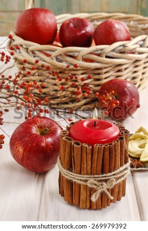 Candle decorated with cinnamon sticks and basket of apples in the background.  - stock photo