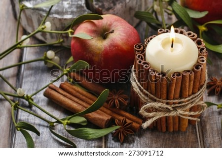 Candle decorated with cinnamon sticks and red apples, christmas decoration - stock photo