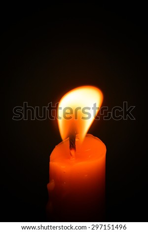 Candle flame closeup isolated on black.