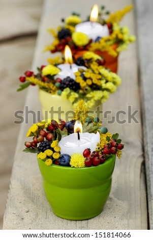 Candle holder decorated with autumn flowers and other plants. Selective focus - stock photo