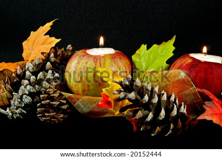 candle in apples with pine cones