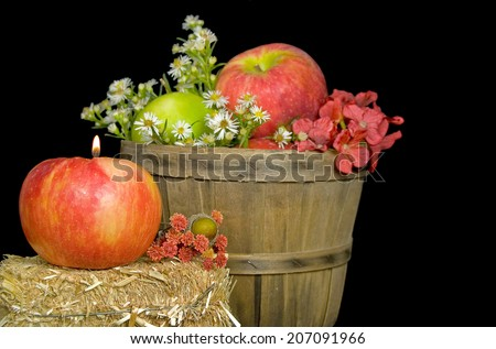 candle in fall apple on a hay bale with bushel basket - stock photo