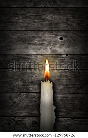 candle in front of old wooden planks - stock photo
