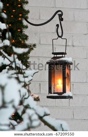 Candle in lantern against white brickwall at Christmastime