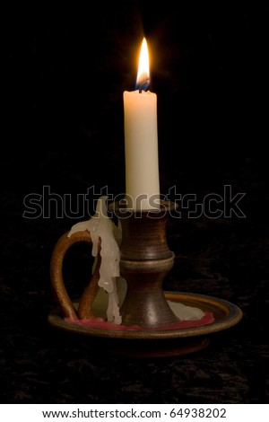 Candle in old fashioned candlestick holder on black background - stock photo