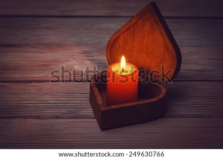 Candle in open heart shaped box on vintage wooden background - stock photo