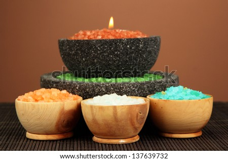 Candle in stone bowl with marine salt, on bamboo mat, on brown background - stock photo