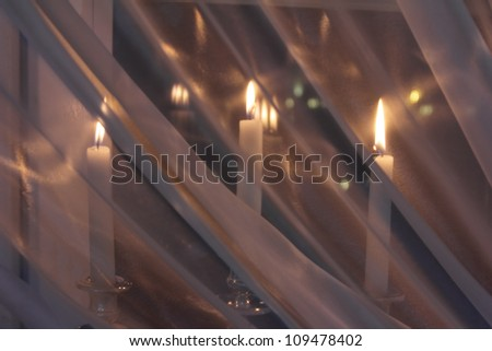 Candle in the window of transparent tulle - stock photo