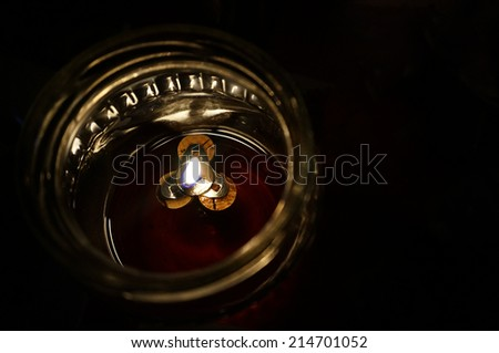 Candle inside a bowl with black isolated background - stock photo
