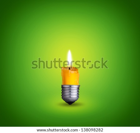 candle into lighting bulb on green background - stock photo