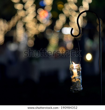 Candle light in glass jar decorated night garden - stock photo