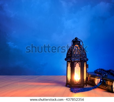 "candle light of muslim style's lantern shining on arabic letters of the name of Muslim God ""Allah"" in heart shape with holy book ""Quran""."