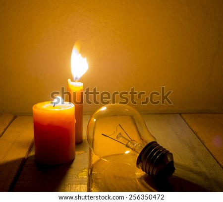 candle light shine on incandescent bulb, no electricity makes electrical equipment useless