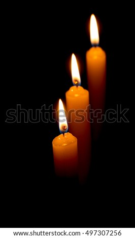 candle lit brightly against a black background
