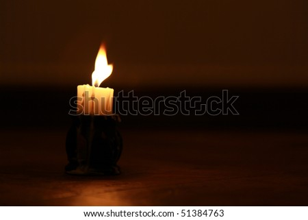 Candle on reflective floor,wax melting