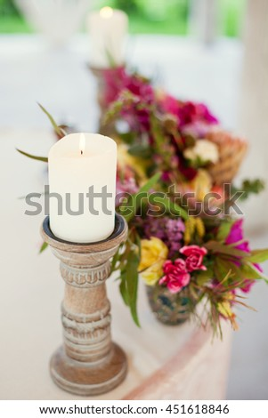 candle on wooden candlestick and smaal bouquets - stock photo