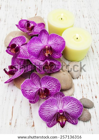 Candle, orchids and massage stones on a wooden background - stock photo