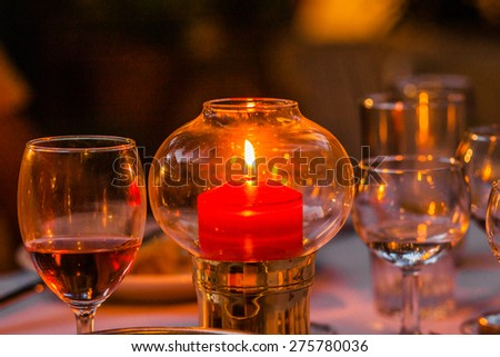 Candle stick in a glass bubble with class of wine on the side - stock photo