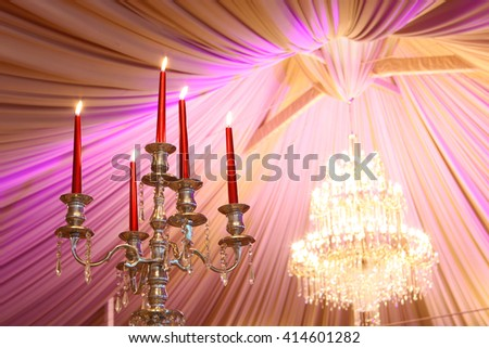 candle stick with lighting candles and a big chandelier in a wedding tent - stock photo