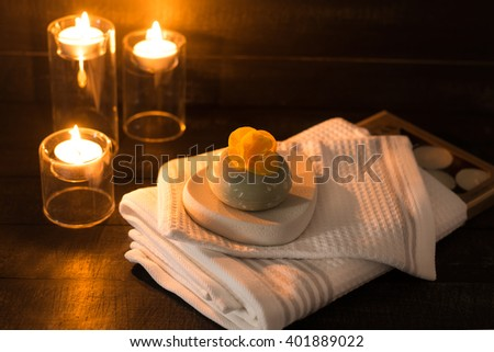 Candle, toweles and soap with a yellow flower on a wooden background spa concept - stock photo
