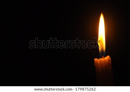 Candle With Flame And Space For Caption Over Dark Background  (Noise Visible Due To Low Light Condition) - stock photo