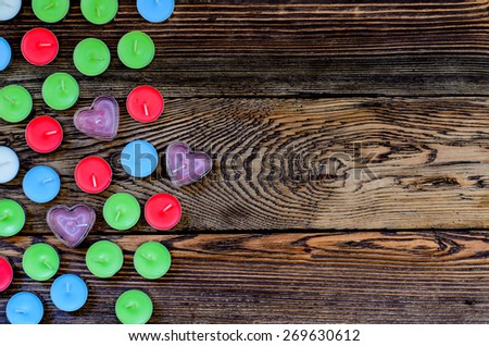 Candle with gift box and hearts on wooden background - stock photo
