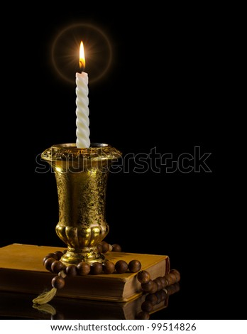 Candle with rosary and antique book