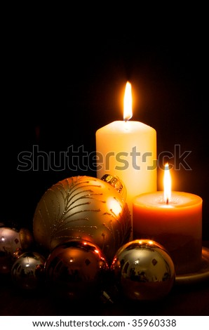 Candles and Christmas decorations on black - stock photo
