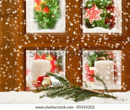 Candles at a festive seasonal window as snow falls onto a pine branch outside - stock photo