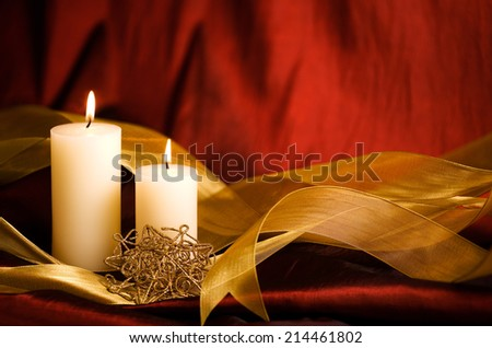 Candles, Christmas decoration and ribbon against a rich red background.  - stock photo