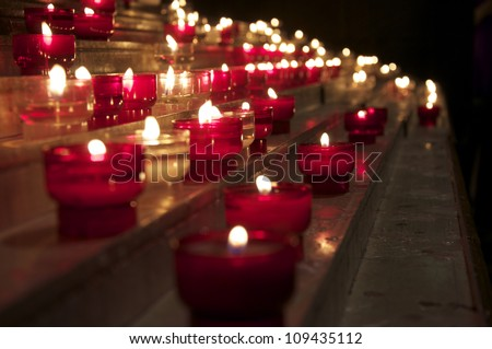 Candles flicker in a church in the beautiful luxurious town of Monaco. July 2011 - stock photo