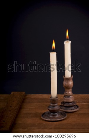 candles in clay candlesticks on a wooden table - stock photo