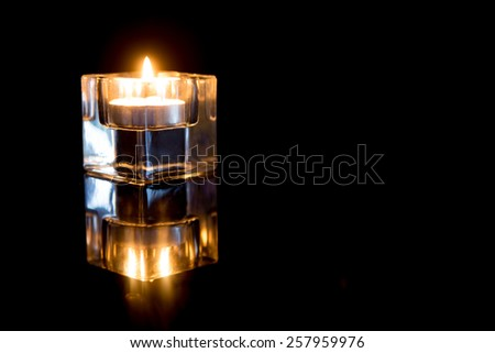 Candles in glass candle holders on a black background. - stock photo