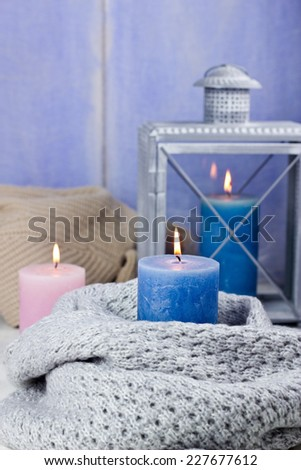 Candles in knitted scarfs, selective focus - stock photo