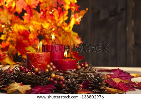 Candles in nice and beautiful colorful autumn leaves - stock photo