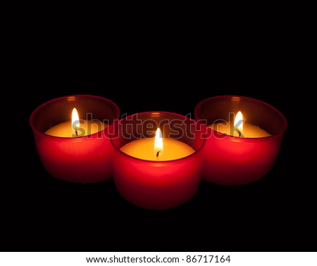 Candles in red holders over black - religious, All Saints Day, Christmas - stock photo