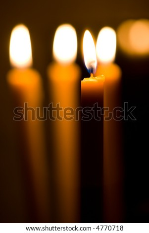 Candles isolated over dark background. Shallow depth of field. - stock photo