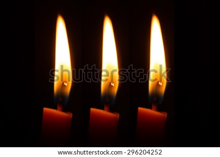 Candles light close up over black, Christmas or general use   - stock photo