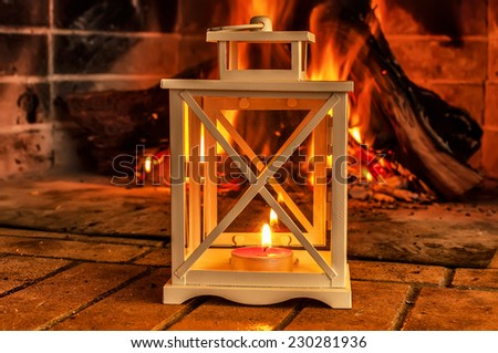 Candlestick with a candle on the background of the fireplace - stock photo
