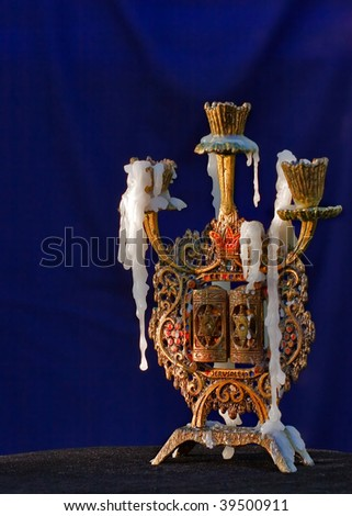 Candlestick with remaining of candles on blue background - stock photo