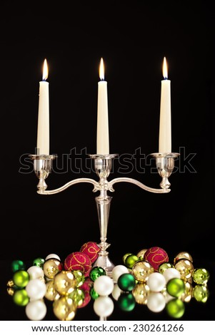 candlestick with three candles, green, gold, pearl and red Christmas tree balls as Christmas and New Year decoration/Christmas and New Year decoration - stock photo